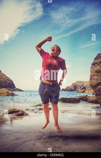 A boy on a sandy beach jumping for joy. A Cornish beach with the ocean behind him. - Stock Image
