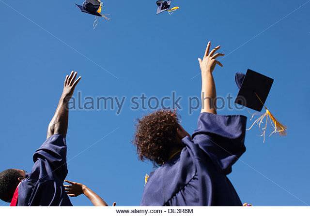 Graduates throwing caps in air outdoors - Stock-Bilder