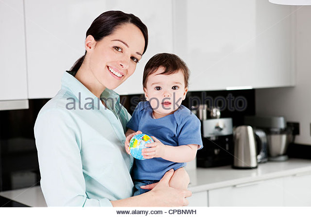 A mother with her baby son, baby holding a globe ball - Stock Image