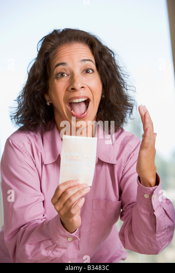 Woman with winning lottery ticket excited and smiling - Stock Image