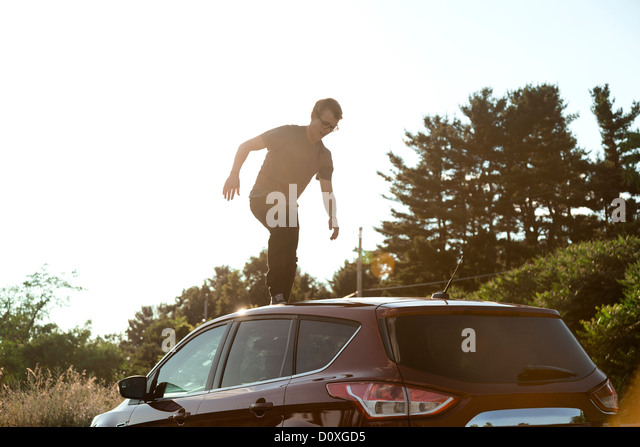 Young man walking across car roof - Stock Image