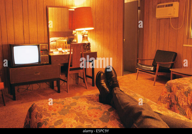 Person watching television in cheap motel room - Stock Image
