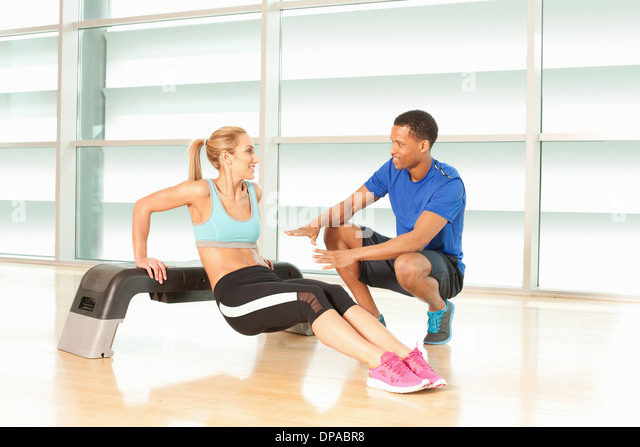 Woman doing exercise on step with man instructing - Stock Image