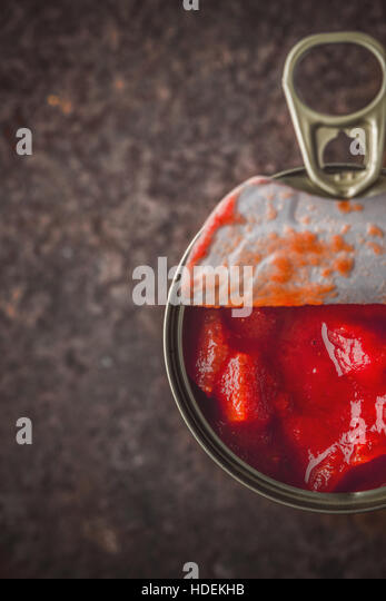 Chopped tomatoes in the metal can in the stone table vertical - Stock Image