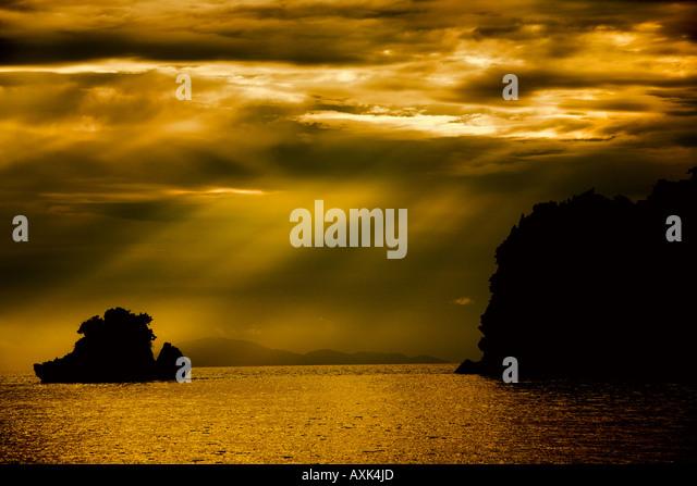 sunlight streak through clouds break apard separate contrast black orange white yellow nature rocks island - Stock Image