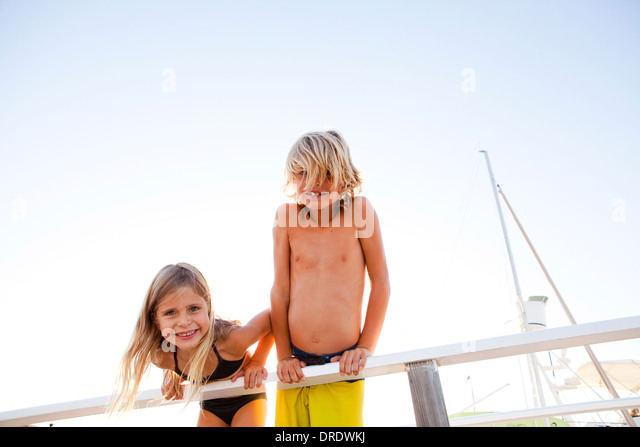 Brother and sister hanging over edge of pier - Stock Image
