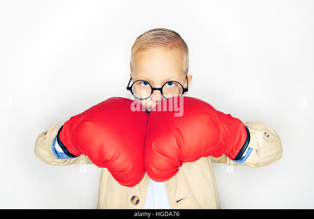 Little boy in glasses and boxing gloves striking hands and looking seriously at camera on studio background. - Stock Image