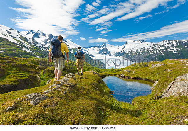 Group of hikers hiking in Portage Pass with Portage Glacier in the background, Chugach National Forest, Alaska, - Stock-Bilder