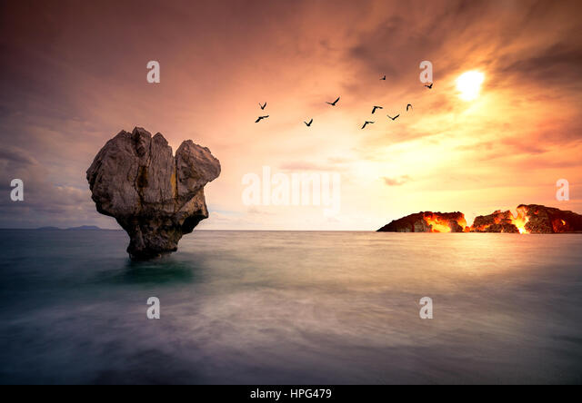 Fine art with lonely rock sculpture in the sea with silhouettes of flying birds and a burning island under sunset. - Stock Image