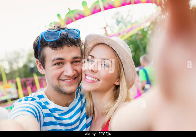Happy couple at fun fair taking selfie - Stock Image