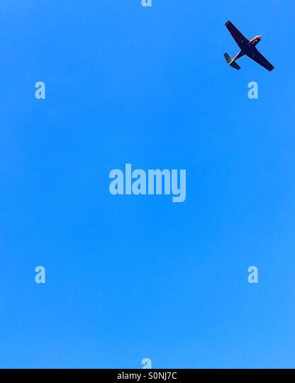 Minimalist plane on blue sky - Stock Image