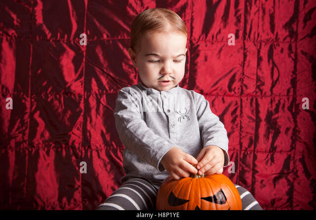 Portrait of a little boy dress up for halloween party. He is playing with a painted pumpkin - Stock Image