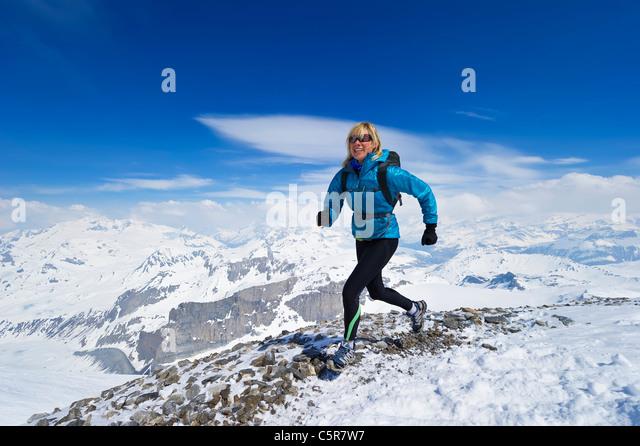 Women enjoying a run across a snowy alpine mountain range. - Stock-Bilder