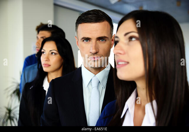 Group of young co-workers standing in a row at office - Stock Image