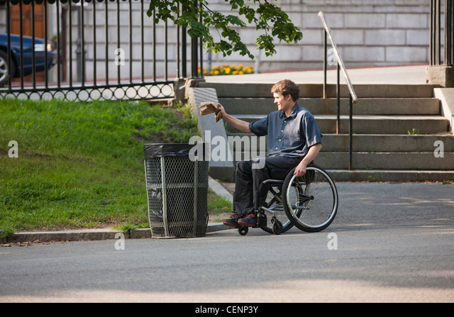 Man with spinal cord injury in a wheelchair putting trash in receptacle at public park - Stock Image