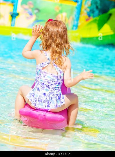 Rear view of sweet little girl wearing beautiful swimwear having fun on water attractions in aquapark, happy childhood, - Stock-Bilder
