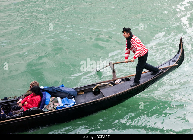 Gondolier rowing a gondola on the Grand Canal , Venice Italy - Stock Image