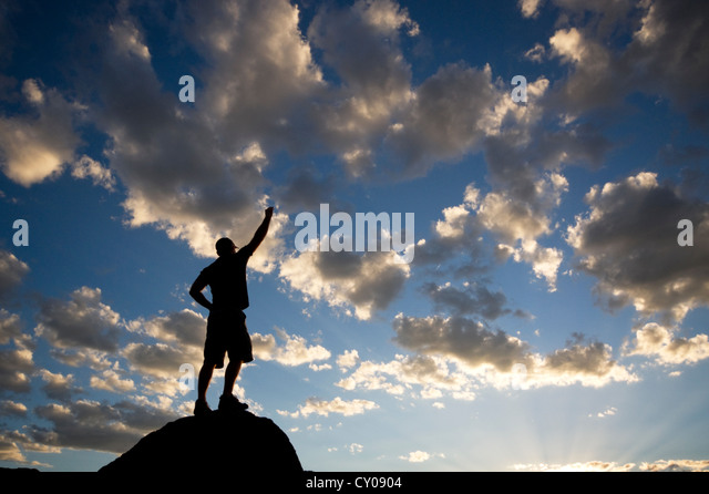 Silhouette of male figure standing on rock with arm raised - Stock Image