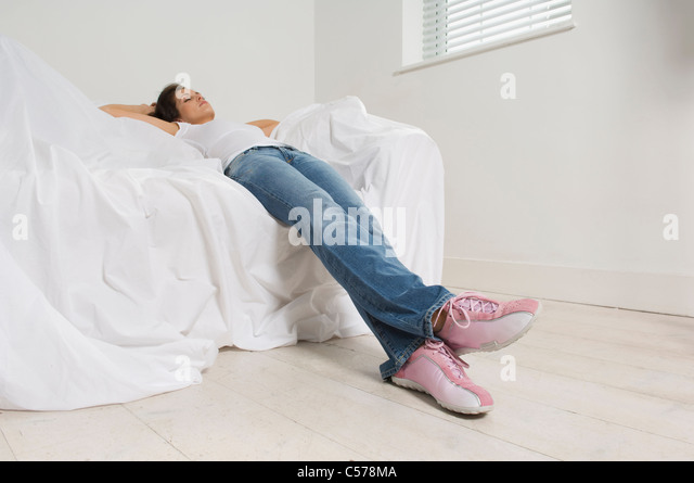 Woman resting on couch in new home - Stock Image