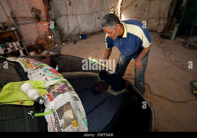 The owner of a car workshop, Santos, polishes a car in Penonome, Cocle province, Republic of Panama. - Stock-Bilder