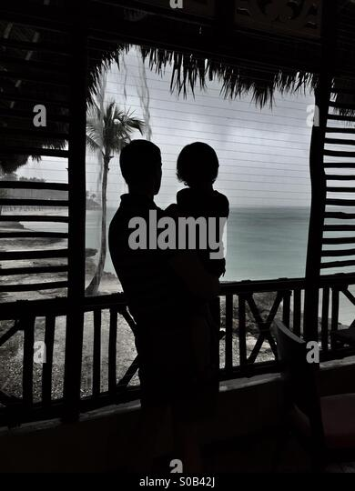 A father and child watch a tropical rain storm pass. - Stock Image