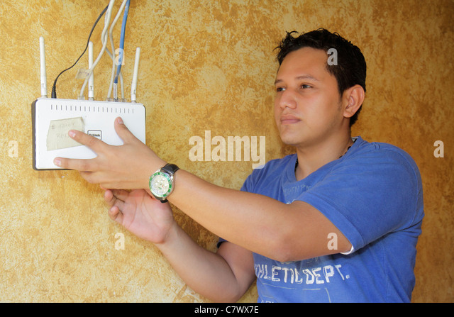 Managua Nicaragua Hotel Villa Angelo repairing Internet wireless router maintenance man technician Hispanic man - Stock Image