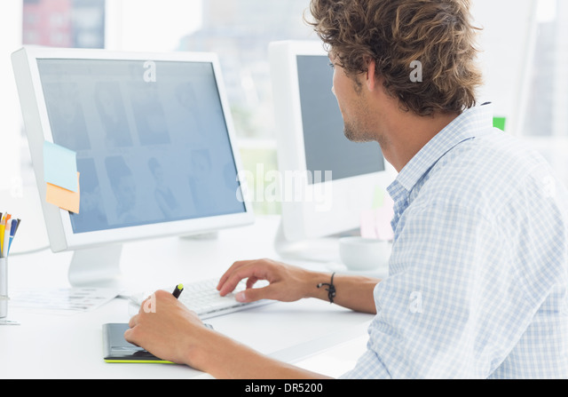 artist drawing something on graphic tablet with pen - Stock Image