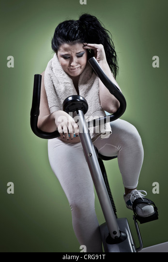 Woman using exercise bike at home - Stock Image