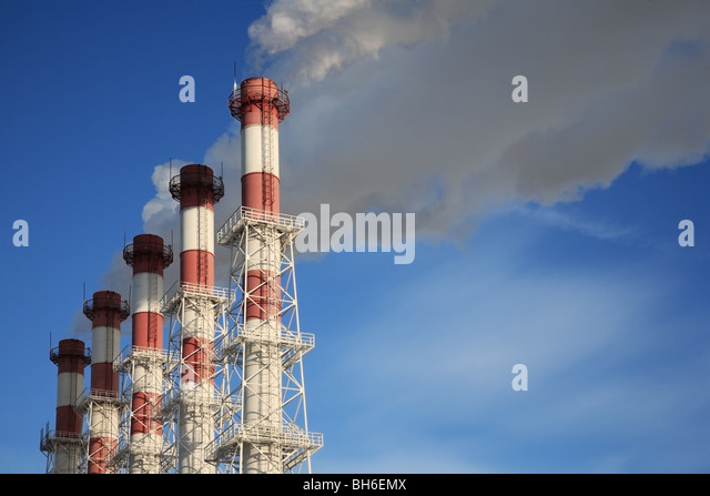 Five chimneys with steam on a blue sky background. - Stock-Bilder