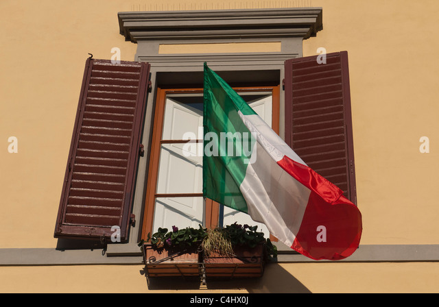 An Italian flag flaps in the breeze from a second floor window in Florence, Italy - Stock Image