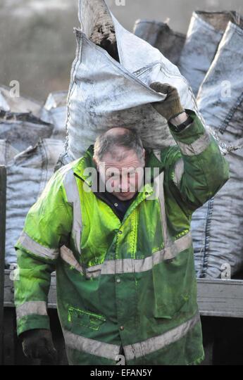 Man delivering sacks of coal, Cornwall, England, UK - Stock Image