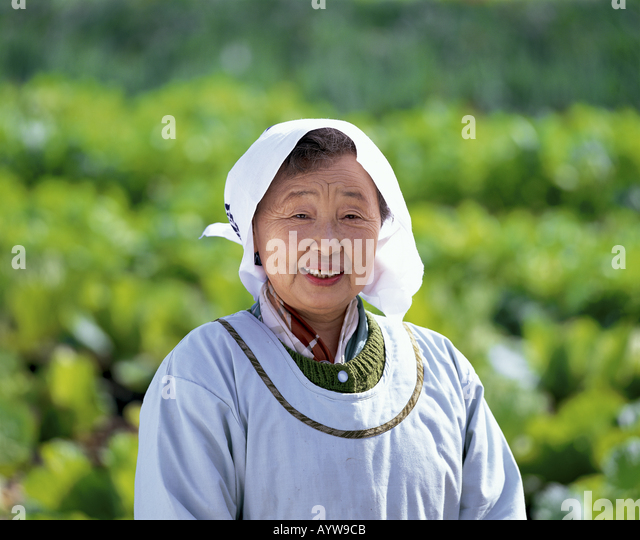 Sinior woman in apron and towel on her head - Stock-Bilder