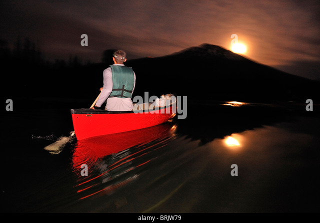 A man canoeing in a red boat at night on a mountain lake in Oregon. - Stock Image
