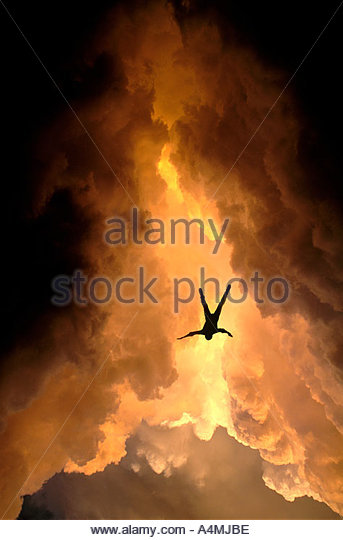 Free falling man falling out of dark stormy golden glowing clouds - Stock Image