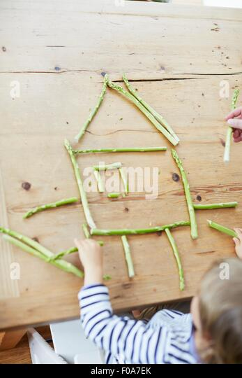 Boy playing with asparagus on dining table - Stock Image