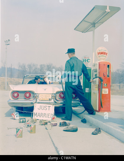 Couple with Just Married sign driving through gas station - Stock-Bilder