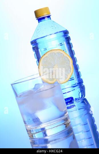 Water glass with lemon and water bottle, Wasserglas mit Zitrone und Wasserflasche - Stock-Bilder