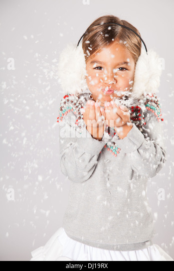 Little girl blows snow - Stock Image