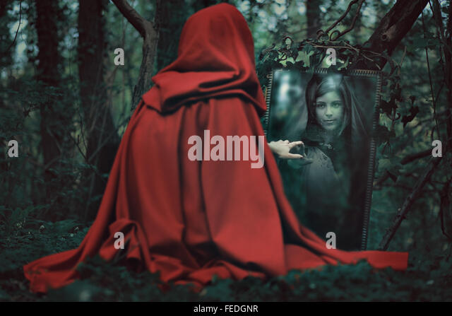 Mysterious red hooded woman in front of a magical mirror. Dark fantasy - Stock-Bilder