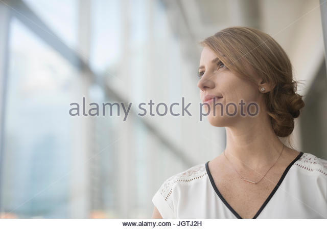 Portrait pensive businesswoman looking out window - Stock Image