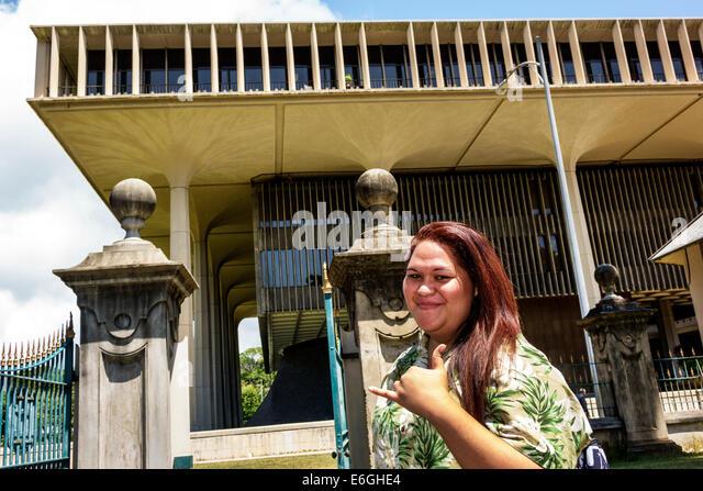 Hawaii Oahu Hawaiian Honolulu State of Hawaii Legislature Building outside woman shaka sign hang loose - Stock Image