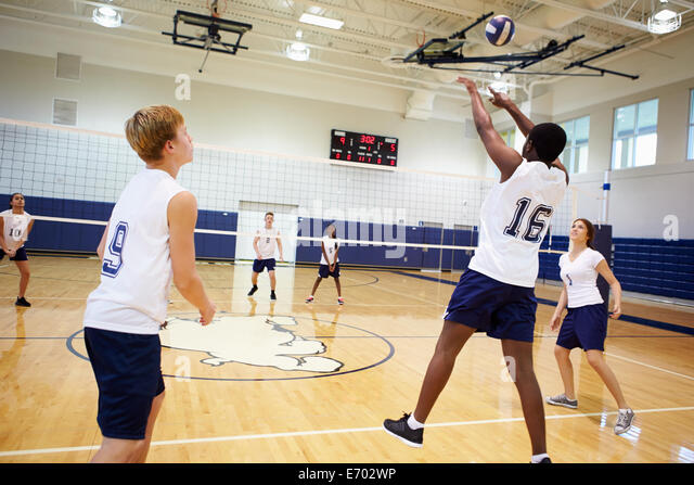 High School Volleyball Match In Gymnasium - Stock Image