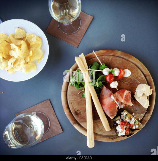 Overhead view of ham, cheese, parmigiana finger food and cherry tomatoes with mozzarella cheese - Stock Image