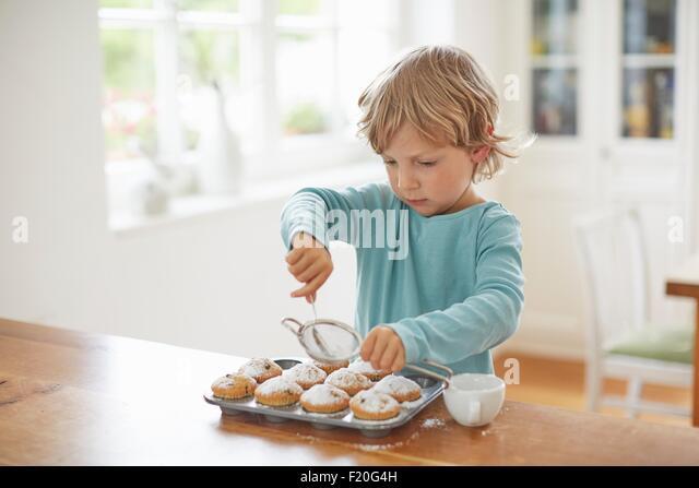 Boy making cupcakes in kitchen - Stock Image