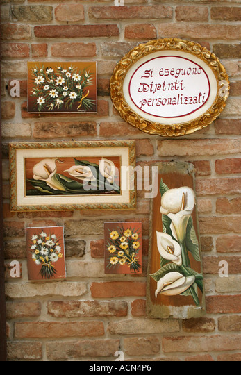 modern paintings hanging on old brick buildings in the hilltown of Sarnano in Le Marche Italy - Stock Image