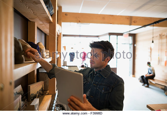 Worker with digital tablet in shop - Stock-Bilder
