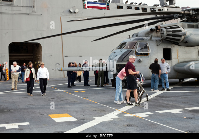 visitors to flight deck USS New York moored at pier 88 New York City gather around fuselage of large lethal Helicopter - Stock Image