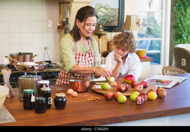 Grandmother and little boy peeling an apple at kitchen - Stock Image