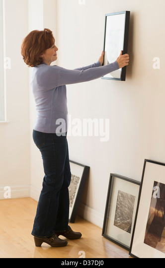 USA, New Jersey, Jersey City, Woman hanging picture on wall - Stock Image
