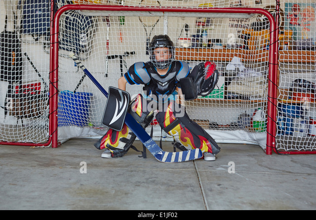 Boy in hockey goal wearing protective sportswear - Stock Image